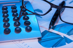 Pen, calculator and glasses in the blue light of the monitor Royalty Free Stock Photography