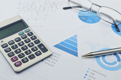 Pen, calculator, glasses on financial chart and graph Royalty Free Stock Photos