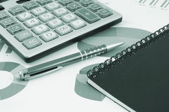 Pen and calculator and notebook Stock Image