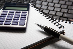 Pen with calculator on a notebook and keyboard Royalty Free Stock Photography