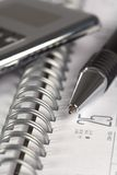 Pen  and calculator on notepad Stock Image