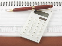 Pen and calculator on open diary notepad. Pen and white calculator on open pages of notepad Stock Photography