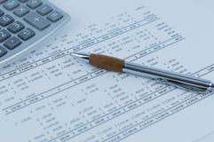 Pen and Calculator over a report. Metallic Pen and calculator over a report with number figures Royalty Free Stock Photos