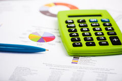 Pen and Calculator on a paper with graph and charts. Stock Image