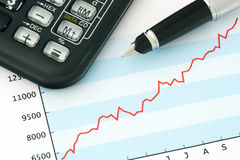 Pen and Calculator on Positive Earning Graph. Financial Graph with Pen and Calculator Royalty Free Stock Images
