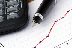 Pen and Calculator on Positive Earning Graph. Positive Earning Graph Royalty Free Stock Photo