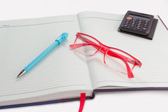 Pen,calculator, red glasses placed on notebook Stock Image