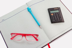 Pen,calculator, red glasses placed on notebook Royalty Free Stock Images