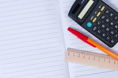 Pen, calculator and ruler on notebook Stock Photo