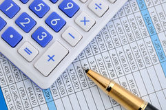 Pen and calculator on sheet with numbers Stock Photos