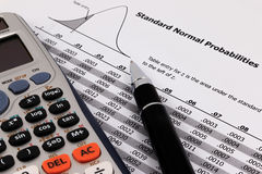 Pen and calculator on standard normal probabilities table. Royalty Free Stock Photography