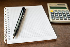 Pen and the calculator on the table Royalty Free Stock Photography