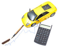 Pen, Car and calculator. A car with a pen and a calculator on a graph Stock Photos