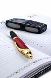 Pen and cell phone on open agenda Royalty Free Stock Photos