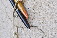 Pen chain and bullet. Pencil chain and bullet symbolically reflect the the situation in the politics Royalty Free Stock Photo