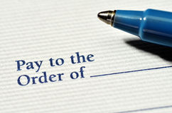 Pen on Check to be Written. Pen on blank check to be written with dollars Royalty Free Stock Image