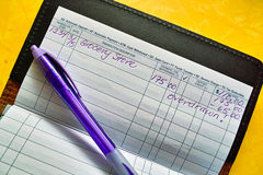 Pen and checkbook register Stock Photography