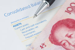 Pen with Chinese banknote on the balance sheet Royalty Free Stock Images