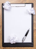 Pen on clear white paper with crumble paper balls on wooden tabl Stock Images