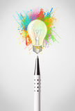 Pen close-up with colored paint splashes and lightbulb Royalty Free Stock Photo