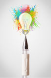 Pen close-up with colored paint splashes and lightbulb Royalty Free Stock Photography