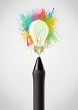 Pen close-up with colored paint splashes and lightbulb. Concept Stock Photo