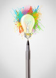 Pen close-up with colored paint splashes and lightbulb. Concept Stock Photography