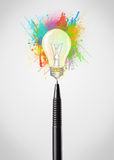 Pen close-up with colored paint splashes and lightbulb Royalty Free Stock Images