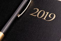 A pen on a closed black notebook diary with the inscription 2019 stock photos