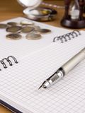 Pen and coin on notebook Stock Image