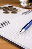 Pen and coin on notepad Stock Image