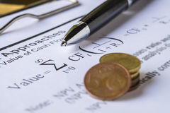 Pen and coins on Discount cash flow model. Royalty Free Stock Photography