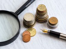 Pen, coins and magnifying glass Stock Photo
