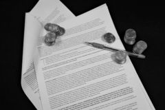 Pen and coins on open contract stock image