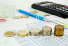 Pen and coins stack on business background Stock Images