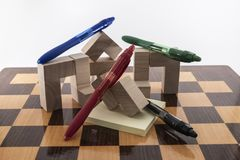 Pens colored. A chess board and pens colored, placed on a white background royalty free stock images