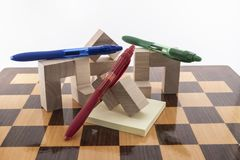 Pens colored. A chess board and pens colored, placed on a white background stock images