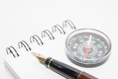 A pen and compass on note book Stock Photography