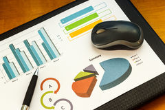 Pen and computer mouse on top business graph. Stock Photography