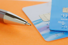 Pen and Credit Cards on an Orange Note Pad Stock Photos
