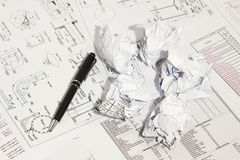 Pen and crumpled papers on engineering drawings. stock photo