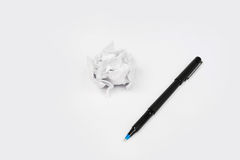 Pen with Crumpled sheet of paper to paper ball on white background Royalty Free Stock Photo