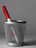 Pen in cup. A red felt pen in a metal cup. The photo has been desaturated apart from the pen Stock Images