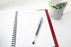 Pen and cup of coffee and notebook. Open a blank white notebook, pen and cup of coffee on the desk Stock Photos