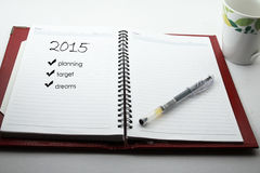 Pen and cup of coffee and notebook with a planning for 2015. Open a blank white notebook, pen and cup of coffee on the desk Stock Photo