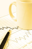 Pen and cup on stock chart. Pen and cup on Forex candlestick chart in yellow lighting Royalty Free Stock Photo