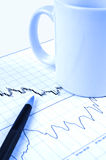 Pen and cup on stock chart. Pen and cup on Forex candlestick chart in blue lighting Stock Photo
