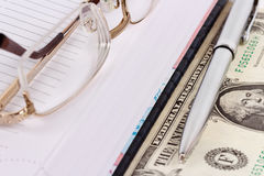 Pen, datebook and glasses. A glasses, a pen, a datebook and a money note Royalty Free Stock Photos