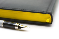Pen and diary. Business a still-life: pen and black diary royalty free stock image