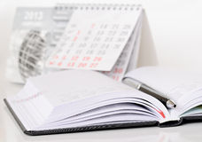 Pen on a diary. Pen on an opened diary and calendar Royalty Free Stock Photos